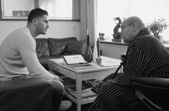 Foto gesprek medewerker met oude man